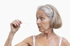 Senior woman checking thermometer against white background Royalty Free Stock Image