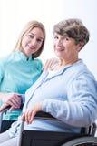 Senior woman and cheerfulness carer. Photo of sick senior women and cheerfulness carer stock image
