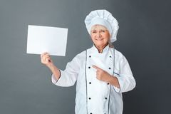 Senior woman chef studio standing isolated on gray pointing at paper looking camera happy royalty free stock photography