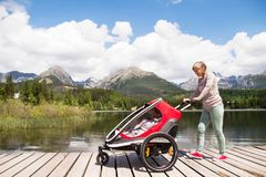 Senior woman and children in jogging stroller, summer day. Senior women and children in jogging stroller at he lake, summer day. High mountains in the Stock Photo