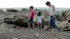 Senior woman and children playing with stones outdoors stock footage