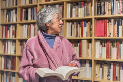 Senior woman choosing a book from the blurry library in the back Stock Image
