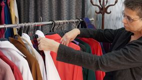 Senior woman is choosing clothes in clothing store. Shopping concept. stock footage