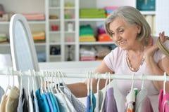 Senior woman choosing shirt in shop. Portrait of senior woman choosing shirt in shop Stock Images