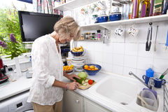Senior woman chopping fresh vegetable while cooking at kitchen counter Royalty Free Stock Photos