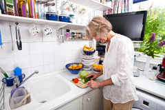 Senior woman chopping fresh vegetable while cooking at kitchen counter Royalty Free Stock Image