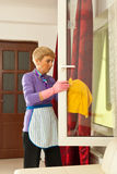 Senior woman cleaning window Royalty Free Stock Image