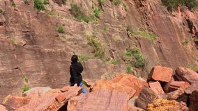 Senior woman climbs over the piled stones in the mountains.. stock footage