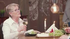 Senior woman clinks a glass of wine with her husband stock video footage