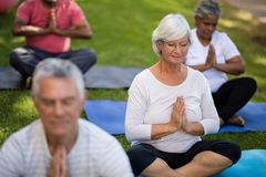 Senior woman with closed eyes meditating while sitting with friends Stock Photos