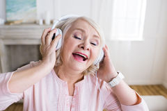 Senior woman with closed eyes wearing headphones and singing Royalty Free Stock Photography