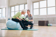 Senior woman and coach looking at health report. Elderly women in a gym sitting on exercise ball and talking to her personal female trainer about exercise plan stock photos