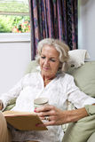 Senior woman with coffee cup reading book while relaxing on armchair at home Royalty Free Stock Photos
