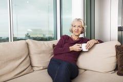 Senior woman with coffee mug sitting on sofa at home Stock Photo