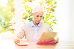 Senior woman with coffee reading newspaper Stock Images