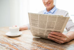Senior woman with coffee reading newspaper at home Stock Image