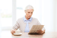 Senior woman with coffee reading newspaper at home Stock Images