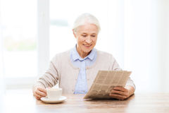 Senior woman with coffee reading newspaper at home Royalty Free Stock Image