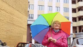 Senior woman with colorful umbrella at building background. Mature woman with colorful umbrella stand outdoors and enjoys view around. Senior woman moves stock video