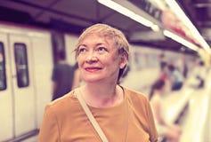 Senior woman commuter waiting train Stock Image