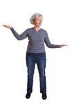 Senior woman comparing imaginary Stock Photography