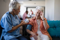 Senior woman complaining about headache to doctor. Senior women complaining about headache to doctor during blood pressure check up at nursing home Royalty Free Stock Photo