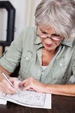 Senior woman completing a crossword puzzle. Senior woman sitting at a table wearing reading glasses concentrating on completing a crossword puzzle stock photography