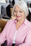 Senior Woman In Computer Class. Smiling senior woman sitting in computer class Royalty Free Stock Images