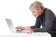 Senior woman concentrating when using her laptop Stock Photography