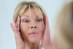 Senior woman concerned about her skin Stock Photography