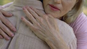 Senior woman condolencing to man about disease or loss, support, care, closeup