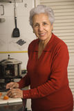 Senior woman cooking. Senior happy woman cooking at kitchen Royalty Free Stock Photography