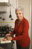 Senior woman cooking. Senior happy woman cooking at kitchen Royalty Free Stock Images