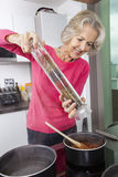 Senior woman cooking food using pepper grinder Royalty Free Stock Photography