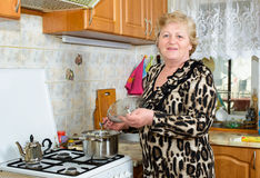 Senior woman cooking. At the kitchen Royalty Free Stock Photography