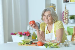 Senior woman cooking in kitchen Royalty Free Stock Image