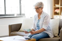 Senior woman counting money at home. Finances, savings, annuity insurance and people concept - senior woman with calculator and bills counting money at home royalty free stock photography