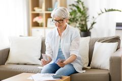 Senior woman counting money at home. Finances, savings, annuity insurance and people concept - senior woman with calculator and bills counting money at home royalty free stock image