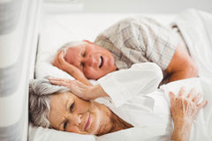 Senior woman covering her ears while man snoring. Senior women covering her ears while men snoring in bed Stock Photo