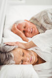 Senior woman covering her ears while man snoring. Senior women covering her ears while men snoring in bed Royalty Free Stock Photos