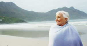 Senior woman covering herself with blanket on beach. During winter stock video footage