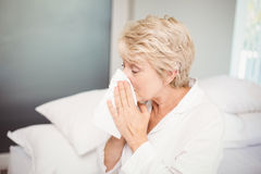 Senior woman covering nose while sneezing at home Royalty Free Stock Photos