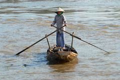 Senior woman crosses Mekong river by a traditional wooden paddleboat in Cai Be, Vietnam. Royalty Free Stock Image