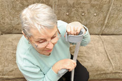 Senior woman with crutch resting Royalty Free Stock Photo