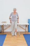 Senior woman with crutches in the hospital gym Royalty Free Stock Image