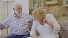 Senior woman crying during quarreling with her husband. Senior man with senior woman sits on sofa at home and discussing something. Old couple are quarreling and stock video
