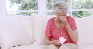 Senior woman crying on the sofa. In slow motion stock video footage