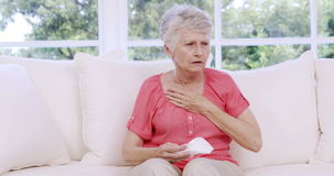 Senior woman crying on the sofa stock footage