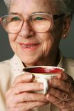 Senior woman and cup of tea. Senior woman relaxing with a warm cup of tea in her hand Royalty Free Stock Image