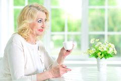 Senior woman with cup of tea. Senior woman sitting at table with cup of tea Royalty Free Stock Images